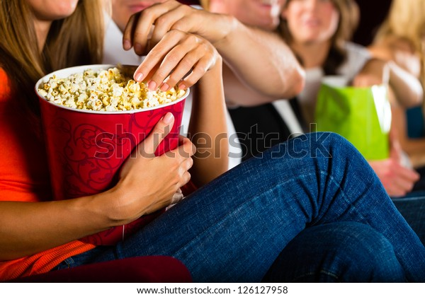 Woman eating large container of popcorn in cinema or movie theater
