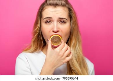Woman eating lemon slice making grimace, pink background