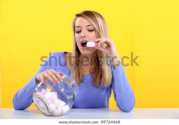 Woman eating marshmallow from jar