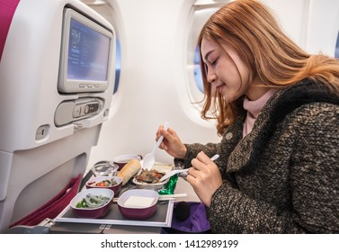 Woman eating meal on commercial airplane in a flight time.