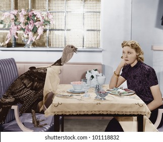 Woman eating meal at table with live turkey