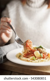 Woman eating meatballs from dish vertical