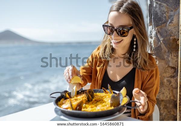 Femme mangeant de la paella, plat traditionnel espagnol, tout en s'asseyant sur la terrasse du restaurant près de l'océan. Concept de nourriture marine et de bonnes vacances d'été