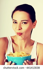 Woman eating pasta from a bowl.