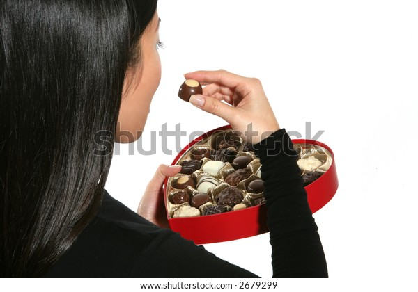 A woman eating a piece of chocolate out of a heart shaped Valentines box