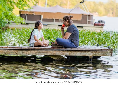 A woman eating a piece of watermelon is talking to her young daughter while sitting on a dock