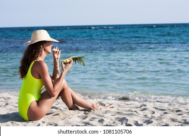 woman eating a pineapple on a beach in summer