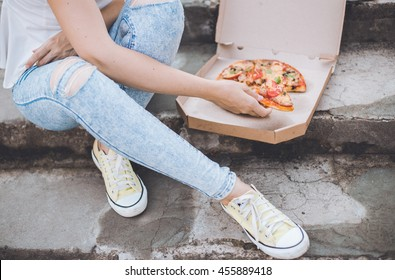 Woman eating pizza outdoor in street .