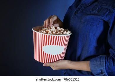 Woman eating popcorn on dark background, closeup