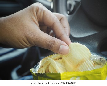 Woman eating potato chip with car