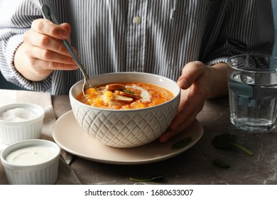 Woman eating pumpkin soup on grey table, close up