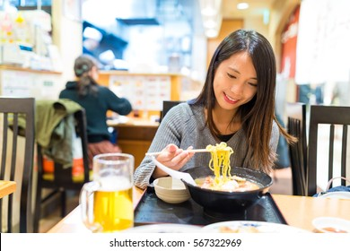 Woman eating ramen in Japanese ramen shop