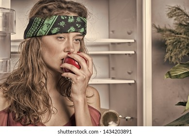 Woman eating red apple at open fridge. Nutrition and diet. Healthy food and vitamin for energy. Forbidden fruit concept, vintage filter