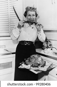 Woman eating roast turkey in her kitchen with a knife in her hand