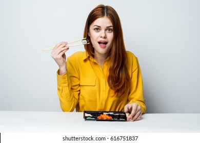 A woman is eating rolls and sushi for lunch