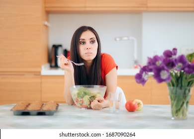 Woman Eating a Salad Alone in the Kitchen Surrounded by Food. Lonely girl stress eating in self isolation procrastinating