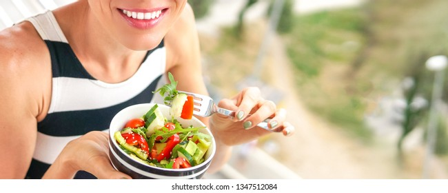 Woman eating salad. Beautiful woman eating salad with a view of the city