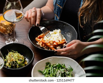 Woman eating salad with burrata at restaurant