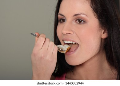 Woman is eating salad with fruits. She is holding fork in hand and putting to open mouth.
