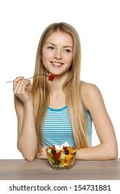 Woman eating a salad, looking to the side at blank copy space, isolated on white background