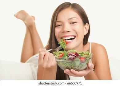 Woman eating salad. Playful smiling woman eating healthy salad in bed. Beautiful cute Caucasian Asian female model.