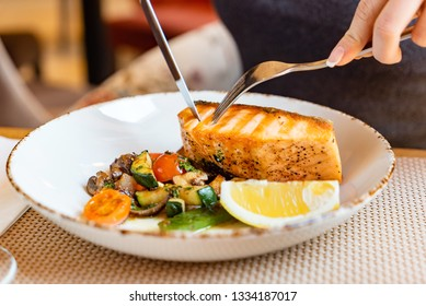 woman eating salmon steak with roasted vegetables