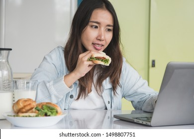 Woman eating sandwich and milk as breakfast during work on laptop at home.
