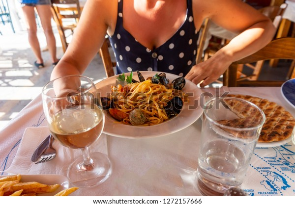 woman eating seafood pasta  in a seafood restautant by the cost in Santorini Oia Amoudi bay