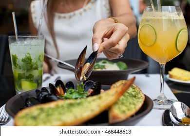 Woman eating seafood in a restaurant. Steamed mussels in white wine sauce. Food Concept