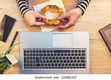 Woman eating sesame bagel for breakfast in office, top view of female hands holding baked snack on working desktop with laptop computer.