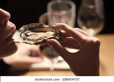 Woman eating shellfish. Seafood and Mediterranean cuisine with mussels in shell. Young woman eating oyster in luxury restaurant. Oyster as healthy delicacy with omega 3 vitamin. Dieting and health.