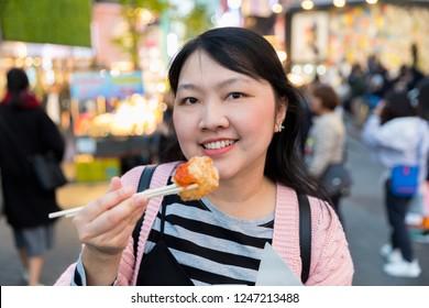 Woman eating shrimp ball Korean food style Street food at Myeongdong market in Seoul South Korea
