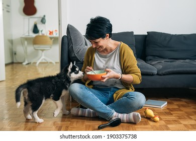 woman eating snack, sitting on the floor in her living room, her dog is beside her