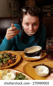 The woman eating soup in the restaurant