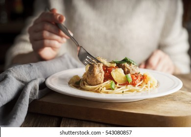 Woman eating spaghetti with meatballs horizontal