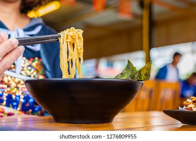 Woman eating a spicy ramen Japanese noodle soup in a black color ramen bowl.