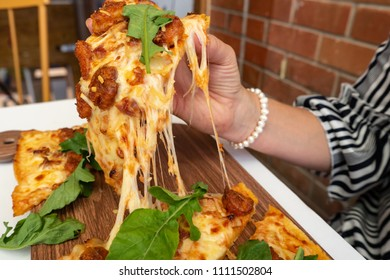 Woman eating square pizza at a restaurant table, hands grabbing a piece of pizza.
