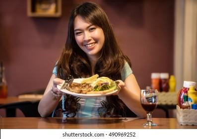 Woman eating steak in a restaurant