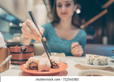 Woman eating sushi food in Japanese restaurant with sticks
