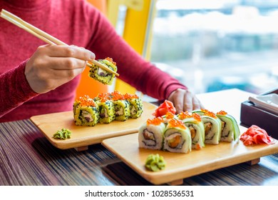 Woman eating sushi rolls at the table - close up photo. Traditional Japanese oriental kitchen with raw fish.