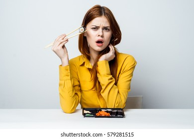 Woman eating sushi at a white table bright woman eating