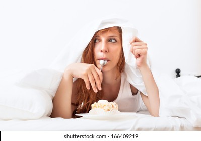 woman eating sweet cake under sheet in bed