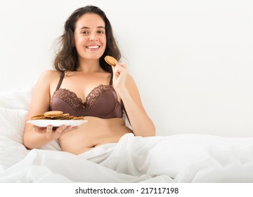 woman eating sweet  chip cookies in bed
