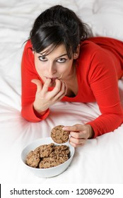 Woman eating sweet cookies in bed. Gluttonous caucasian brunette girl enjoying delicious food. Finger in mouth and guilty looking.