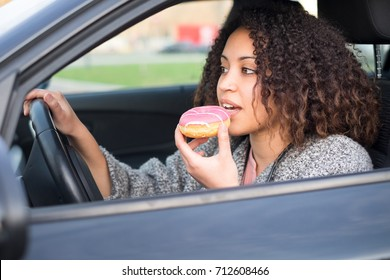 Woman eating a sweet driving her car