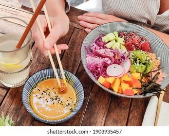 Woman eating tasty colorful healthy natural organic vegetarian Hawaiian poke bowl using asian chopsticks on rustic wooden table. Healthy natural organic eating concept.