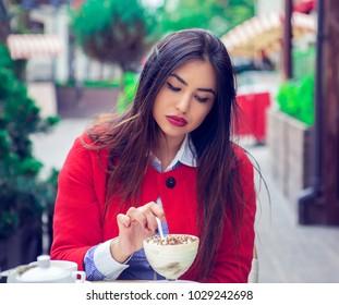 Woman eating tiramisu desert in a french italian restaurant.