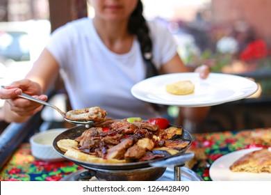 Woman eating the traditional Azerbaijani meal - Saj. Lamb with vegetables