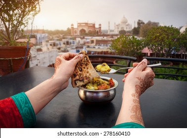 Woman eating traditional Indian food in rooftop restaurant with Taj Mahal view in Agra, Uttar Pradesh, India