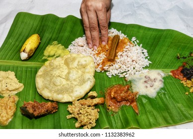 Woman eating traditional Onam Sadhya boiled rice served with curries Parippu, Sambar, Rasam, Pulisseri, Avial, Papadum, Payasam on banana leaf with hand in Kerala, South India on festival day.